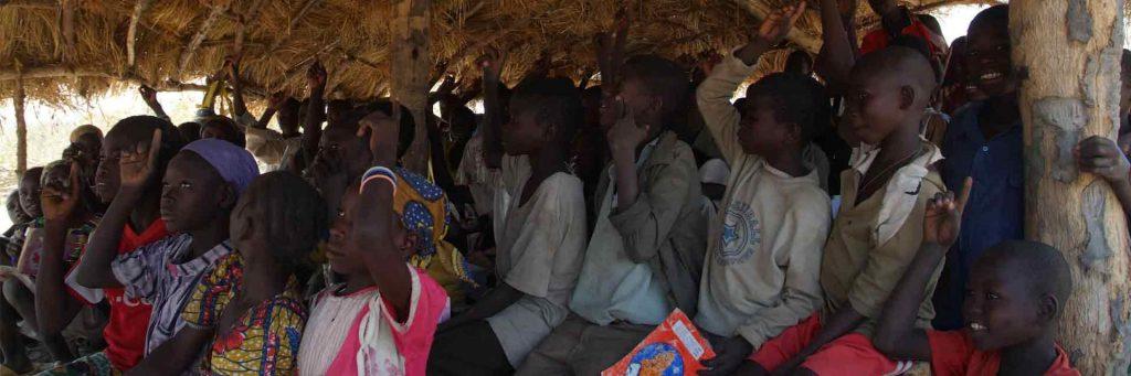 Grupo de niños aisten a una escuela chamizo tradicional