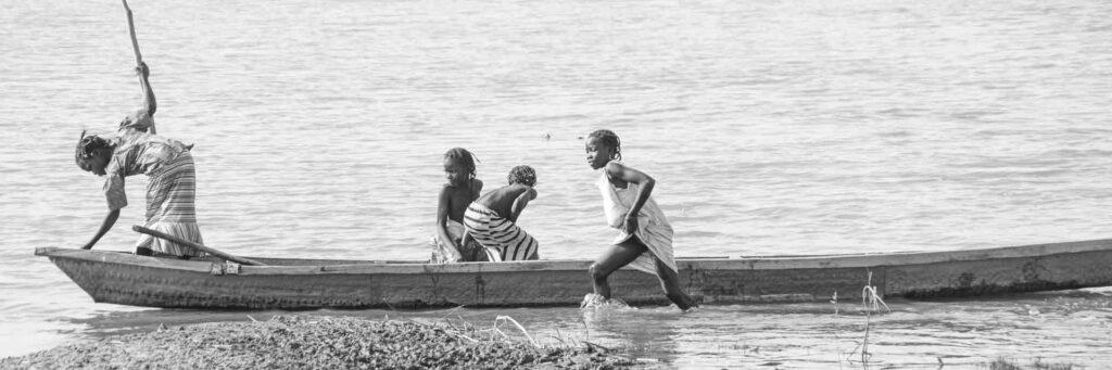 Grupo de niñas chadianas manejan una barca en el Logone