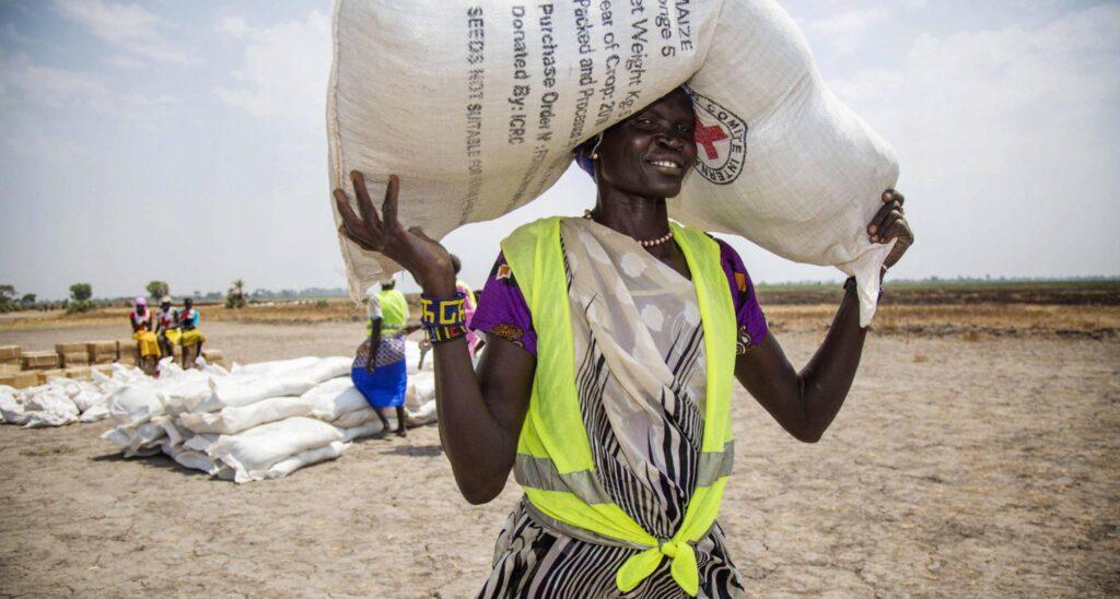 Una voluntaria carga un saco de semillas distribuido por la Cruz Roja Internacional en la ciudad de Thonyor, Sudán del Sur. ALBERT GONZÁLEZ FARRAN AFP PHOTO